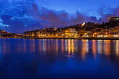 Twilight along the riverfront with lights reflecting in the Douro River in Porto, Portugal Stock Photos