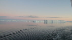 Twilight in Antarctic Sound with icebergs. Sailing through calm waters of Antarctic Sound, Antarctica with field of tabular icebergs at sunset stock video
