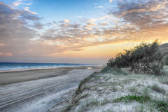 Twilight beach. Sunset on a australian beach, blue and gold sky, ocean and sand dunes Stock Image