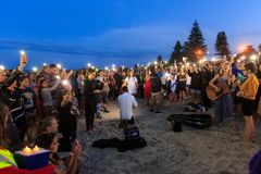 Twilight beach vigil for terrorism victims. Mount Maunganui, New Zealand royalty free stock image