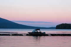 Twilight Boat On Lake. Twilight colors the sky as boat rests peacefully on Odell Lake in Oregon Stock Photos