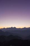 Twilight on Cattle Back Mountain with moon in the sky. Panorama view of the twilight and moon in the sky with silhouette of mountains and cloudscape on top of stock image
