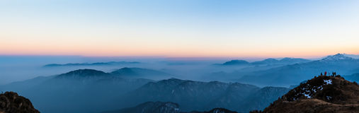Twilight on Cattle Back Mountain. Panorama view of the twilight with silhouette of mountains and cloudscape on top of Cattle Back Mountain (Niubeishan) in stock photography