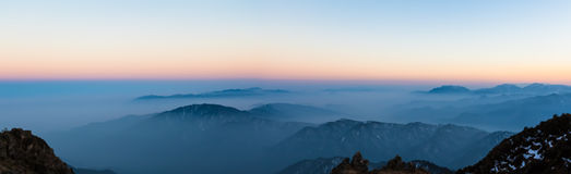 Twilight on Cattle Back Mountain. Panorama view of the twilight with silhouette of mountains and cloudscape on top of Cattle Back Mountain (Niubeishan) in royalty free stock photo