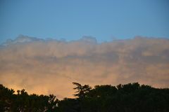 Twilight clouds above forest Stock Photo