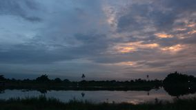 Twilight clouds over the fish pond stock video
