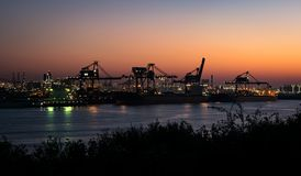 Silhouette of cranes and lights along the waterside of Eurpoort, near Rotterdam, The Netherlands. royalty free stock image