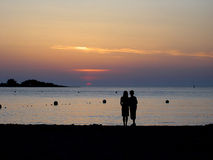 Twilight couple. Lights and shadows in the twilight. Beach in Ibiza. Spain Stock Image