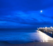 Twilight dusk landscape of pier stretching out into sea with moo Royalty Free Stock Photos