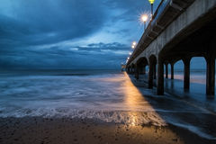Twilight dusk landscape of pier stretching out into sea with moo Stock Photos