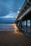 Twilight dusk landscape of pier stretching out into sea with moo Royalty Free Stock Photo