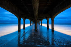 Twilight dusk landscape of pier stretching out into sea with moo Royalty Free Stock Image