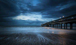 Twilight dusk landscape of pier stretching out into sea with moo Stock Photography