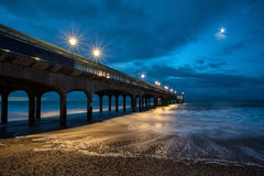 Twilight dusk landscape of pier stretching out into sea with moo Stock Images