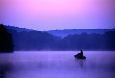 Twilight Fisherman. An angler spends a quiet morning on the lake fishing for bass royalty free stock photo