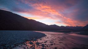 Alpine Sunset in New Zealand. Twilight glow in the clouds over a glacier river Stock Images