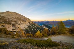 Twilight high up in the Alps. High altitude alpine landscape at dusk with panoramic view of misty valley and harshly eroded mountain range Stock Images