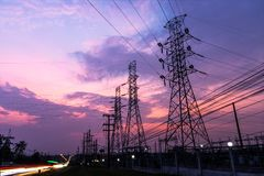 Twilight high voltage. Silhouette of columns and high voltage wires In the power supply station There is a twilight background and have many car traffic royalty free stock image