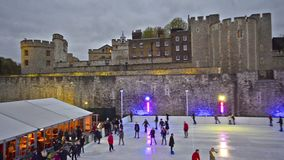 Twilight ice skating scene on the ice rink at Tower of London. London - circa DEC 2013: Twilight ice skating scene on the ice rink at Tower of London in the city stock footage