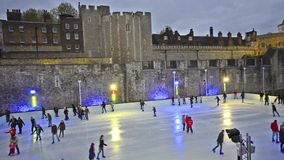 Twilight ice skating scene in London, UK. London - circa DEC 2013: Twilight ice skating scene on the ice rink at Tower of London in the city of London, United stock video