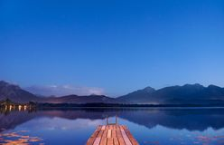 Twilight at lake Hopfensee in Bavaria with pier and mountains mirroring in water. Sunset at lake Hopfensee in Bavaria with wooden pier and mountains mirroring in Stock Photo