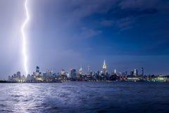 Twilight lightning strike in Midtown Manhattan, New York City skyscrapers. Lightning striking Midtown New York City skyscrapers at night. Stormy skies over Stock Photo
