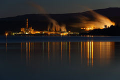 Twilight Mill. The lights of a pulp mill reflect in Georgia Strait in the early morning. Powell River, British Columbia, Canada Stock Images
