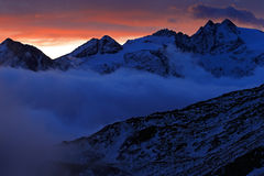 Twilight in the mountain. Foggy morning in Italian Alps, early morning in the mountain with snow during violet twilight, hills in Royalty Free Stock Images