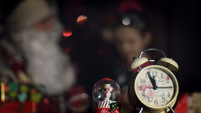In the twilight of the night, in the foreground is an alarm clock, in the background Santa Claus hugs a cute little girl stock footage