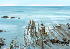 Twilight ocean coast with ribbed stratiform rock. Stock Photography