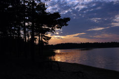 Twilight over the lake. Dark beautiful sunset on the pine forest lake Royalty Free Stock Photo