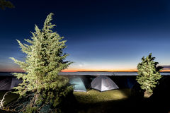 Twilight over sea with many camped tents. Many tents camping near sea at sunset Royalty Free Stock Photography