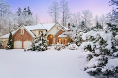 Twilight over snowy home Royalty Free Stock Image