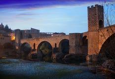 Twilight photo of Medieval bridge with city gate. Besalu Stock Photo