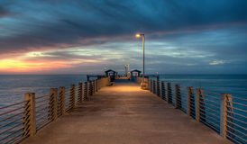 Twilight on the Pier. A lamp lights a long pier as the sun sets over the Gulf of Mexico Stock Photos