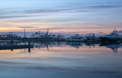 Twilight in the port of Valencia cranes working loading transport ships skyline reflected Stock Photo