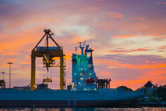 Twilight scene of the cargo ship unloading. Stock Photos