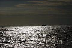 Twilight seascape. Silhouetted boat on horizon of sea at twilight Stock Photo