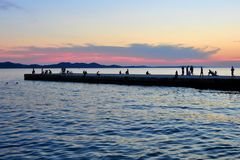 Twilight at the seashore with people at the pier. Idyll dusk. Beautiful atmosphere on the pier. People relax at the shore . Croatia Adriatic sea Stock Images