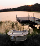 Twilight Serenity. Twilight landscape by the lake with boat by the dock Stock Images