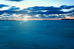 Twilight sky above the blue sea on background of rising sun Stock Photos