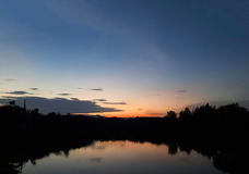 Twilight sky with lake and silhouette trees Royalty Free Stock Image