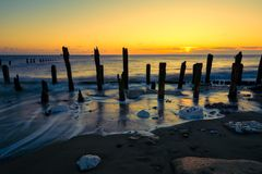 Twilight sky over soft motion sea and wooden posts. Spurn Point, East Yorkshire, UK. Sunrise over beach at Spurn Point Nature Reserve as tide washes around old Stock Images