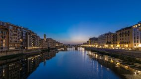 Twilight sky scene of Ponte Santa Trinita Holy Trinity Bridge day to night timelapse over River Arno. With reflections on water and old houses on the side, View stock video footage