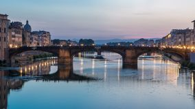 Twilight sky scene of Ponte Santa Trinita Holy Trinity Bridge day to night timelapse over River Arno. With reflections on water, View of after sunset down at stock video