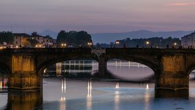 Twilight sky scene of Ponte Santa Trinita Holy Trinity Bridge day to night timelapse over River Arno. With reflections on water, View of after sunset down at stock video footage