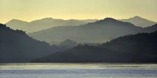 Twilight before sunrise on the ocean coast. Ocean and mountains. Landscape at the foggy morning. Komodo Island. Moluccas, Indonesian Maluku, Spice Islands Stock Images