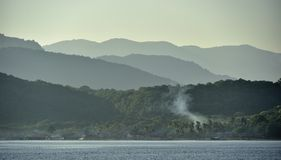 Twilight before sunrise on the ocean coast. Ocean and mountains. Landscape at the foggy morning. Komodo Island. Moluccas, Indonesian Maluku, Spice Islands Stock Photo