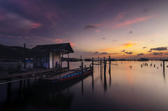 Twilight time on the Songkhla lake, Thailand. Twilight time on the lake with house, boat and wood bridge Stock Photos