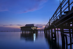 Twilight time on  the Songkhla lake, Thailand. Twilight time on  the lake with house and wood bridge Royalty Free Stock Photography